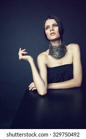 Beautiful brunette woman in decorative silver necklace on dark studio background
