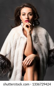 A beautiful brunette woman dressed in a fur coat thrown over her shoulders sits elegantly and thoughtfully on a chair on a gray background. Advertising and commercial design. Copy space.