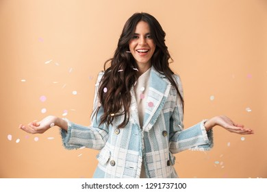 Beautiful brunette woman dressed in plaid jacket standing under confetti shower isolated over beige background