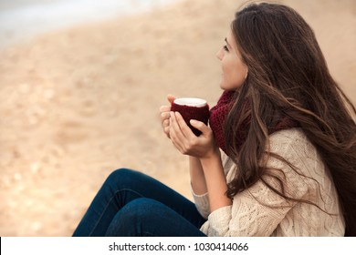 Beautiful brunette woman drinking coffee at morning on the beach and enjoying life