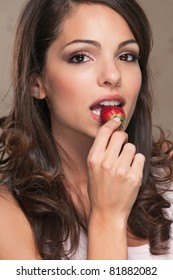 A beautiful brunette woman eating a ripe strawberry