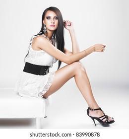 Beautiful brunette woman with elegant white dress. Fashion photo
