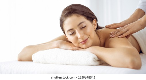 Beautiful brunette woman enjoying back massage with closed eyes. Spa and medicine concept