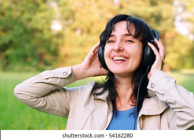 Beautiful brunette woman enjoys the music in headphones outdoors on the meadow