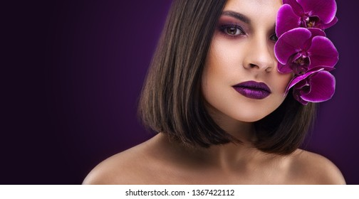 Beautiful brunette woman. evening make-up with purple orchids on the dark background