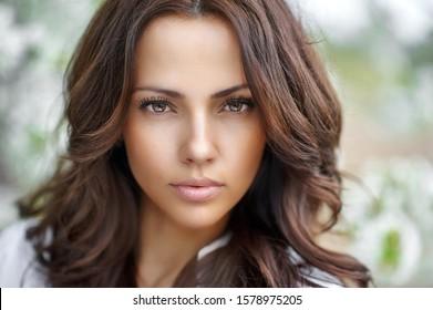 Beautiful brunette woman face close up - perfect skin