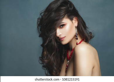 Beautiful Brunette Woman Face. Young Sexy Female Model with Healthy Curly Hair, Necklace  and Earrings with Ruby and Garnet Stone on Blue Background