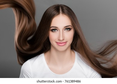 Beautiful brunette woman with gorgeous shiny  long flying hair looks at the camera. Care of  hair