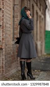 Beautiful brunette woman in grey coat walking in the city. Woman against brickwall.