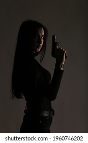 Beautiful brunette woman with a gun in her hand in shadows