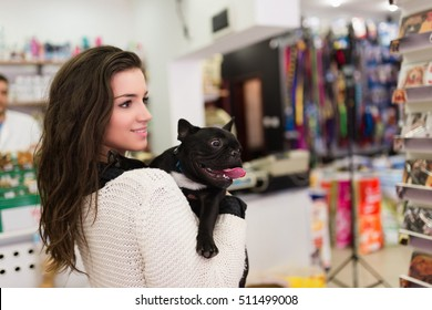 Beautiful brunette woman with her French bulldog puppy in pet shop. Selective focus on dog.