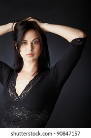 beautiful brunette woman holding her hands in the hair on dark background wearing black lace top.
