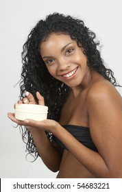 Beautiful brunette woman holding a jar of body butter on white background. Not isolated