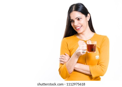 521ec103ff637a Beautiful brunette woman holding transparent cup with tea looking aside - white  background
