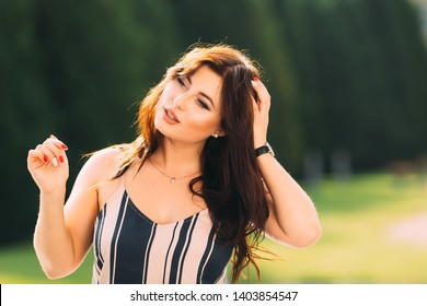 beautiful brunette woman holds her hand in her hair and says something