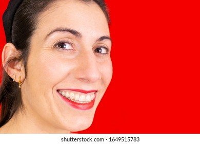 Beautiful brunette woman with invisible brackets in her hand and smiling at the camera, dental concept, healthy and perfect smile on red background