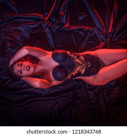 beautiful brunette woman with lingerie lying on a velvet cloth, wearing a gold corset and metal pieces