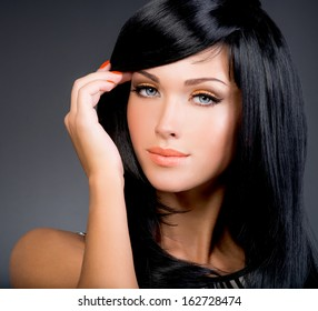 Beautiful brunette woman with long black straight hair posing at studio