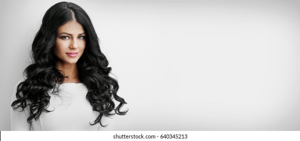 Beautiful brunette woman with long curly hair on white background with copy space