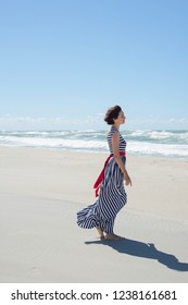 Beautiful brunette woman in a long dress walks along the seashore