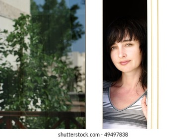 Beautiful brunette woman looking from the balcony with garden reflection in the window