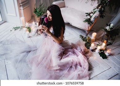beautiful brunette woman in a lush pink tulle dress sits on a white wooden floor near a sofa decorated with flowers and candles and curtains holds a flower in her hands and dreams of smiling
