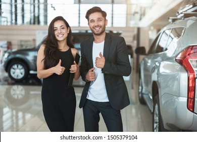 beautiful brunette woman manager and her handsome man colleague standing in dealership center after succesful deal showing like signs feeling happy