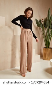 Beautiful brunette woman natural make up wear fashion clothes casual dress code office style black blouse and beige pants suit for romantic date business meeting accessory interior stairs flowerpot.