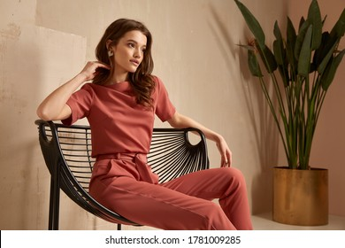 Beautiful brunette woman natural makeup wear fashion clothes casual dress code office style total pink blouse and pants suit, romantic date business meeting accessory armchair interior stairs