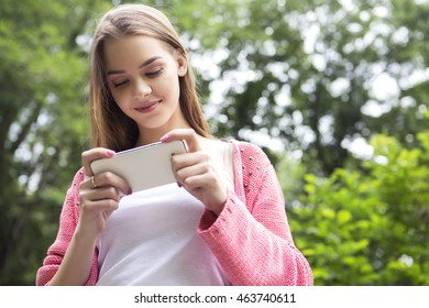 Beautiful brunette woman in neutral casual outfit walking in park, texting sms using her phone, smiling. Lifestyle portrait. Copy space