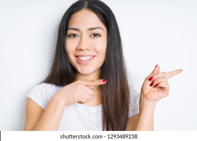 Beautiful brunette woman over isolated background smiling and looking at the camera pointing with two hands and fingers to the side.