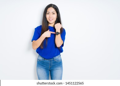 Beautiful brunette woman over isolated background In hurry pointing to watch time, impatience, upset and angry for deadline delay