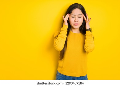 Beautiful brunette woman over yellow isolated background with hand on head for pain in head because stress. Suffering migraine.
