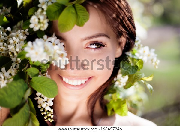 beautiful brunette woman in the park standing near the apple tree on a warm summer day