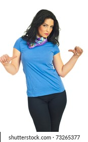 Beautiful brunette woman pointing with thumbs to her blank blue t-shirt isolated on white background