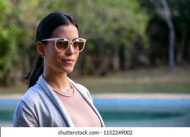 A beautiful brunette woman at the pool wears a dark glasses with a beige lens, a pearl necklace and a neutral-colored female blazer. Social Commitment. Model. Golden hour