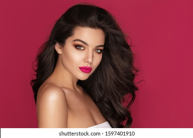 Beautiful Brunette Woman Portrait with brown eyes and Healthy Long Shiny Wavy black hair. Volume shampoo. Attractive Beauty model with professional make up against pink background