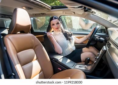 Beautiful brunette woman posing inside car with key