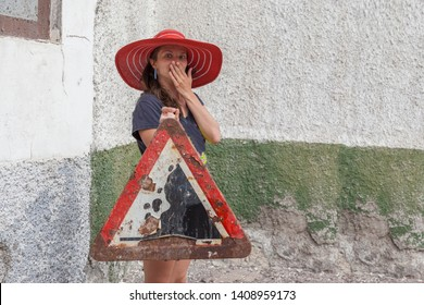 """Beautiful brunette woman in red sombrero hat is holding rusty dangerous warning road sign """"debris ahead"""" - falling rocks - she is surprised standing near collapsing building closing her face"""