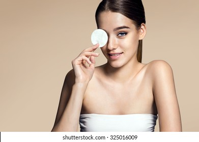 Beautiful brunette woman removing makeup from her face. Photo of attractive brunette girl, skin care concept