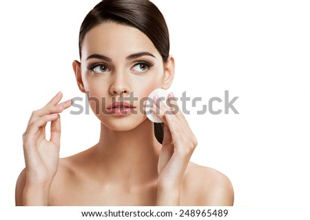 Beautiful brunette woman removing makeup from her face, skin care concept / photo composition of brunette girl - isolated on white background