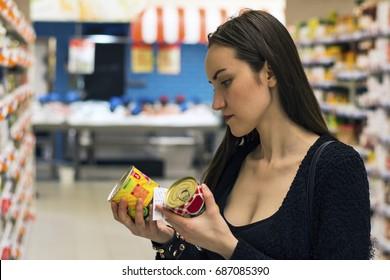 Beautiful brunette woman shopping in supermarket. Choosing non-GMO food