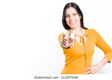 932ee6c2b24680 Beautiful brunette woman showing glass of filtered water to drink - white  background