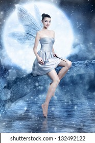 Beautiful brunette woman as silver fairy on night sky with wings and magic wand