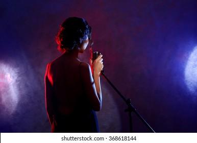 Beautiful brunette woman singing on purple background, backside view