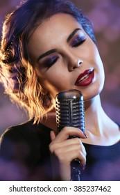 Beautiful brunette woman singing on grey background