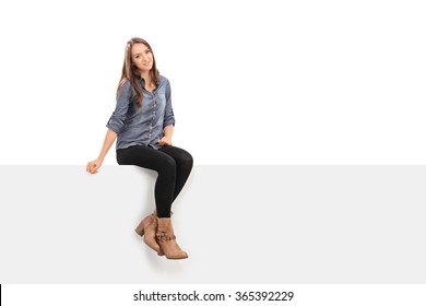 Beautiful brunette woman sitting on a blank white signboard and looking at the camera isolated on white background