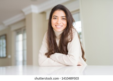 Beautiful brunette woman smiling cheerful with big smile, looking positive and happy with crossed arms