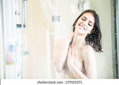 Beautiful brunette woman taking shower after long stressful day.Woman showering and enjoying bath.Using douche shower gel,body lotion,shower relaxing muscles.Depilation and anti cellulite treatment.