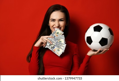 Beautiful brunette woman in tight red dress hold soccer ball in one hand and bites a wad of dollars on red background